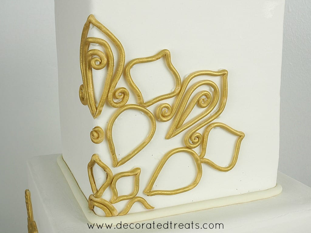 Gold fondant lace on a square cake