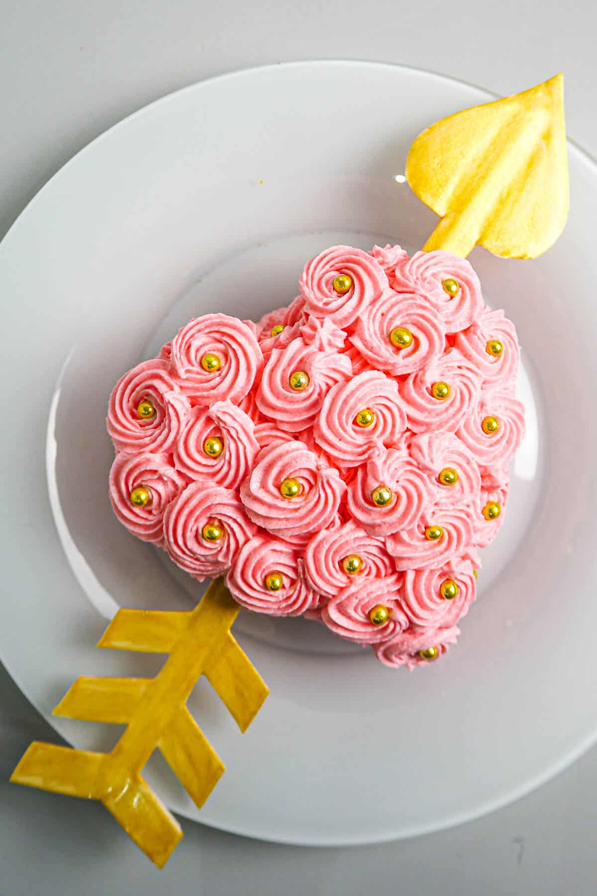 A heart shaped cake decorated with pink buttercream rossettes and a gum paste arrow going through it