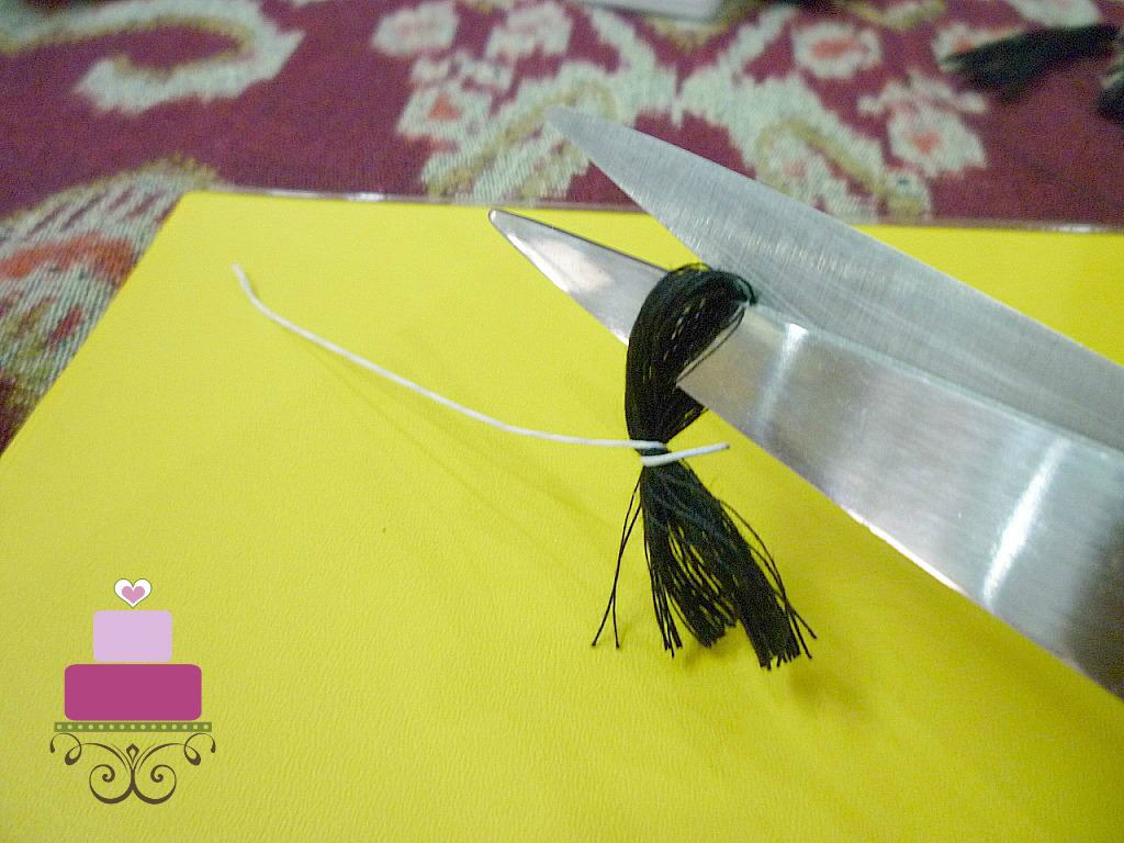 Using a pair of scissors to cut a loop of black thread