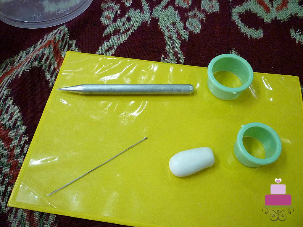 A wire, thin rolling pin, 2 round green cutters and a piece of gum paste on a green mat.
