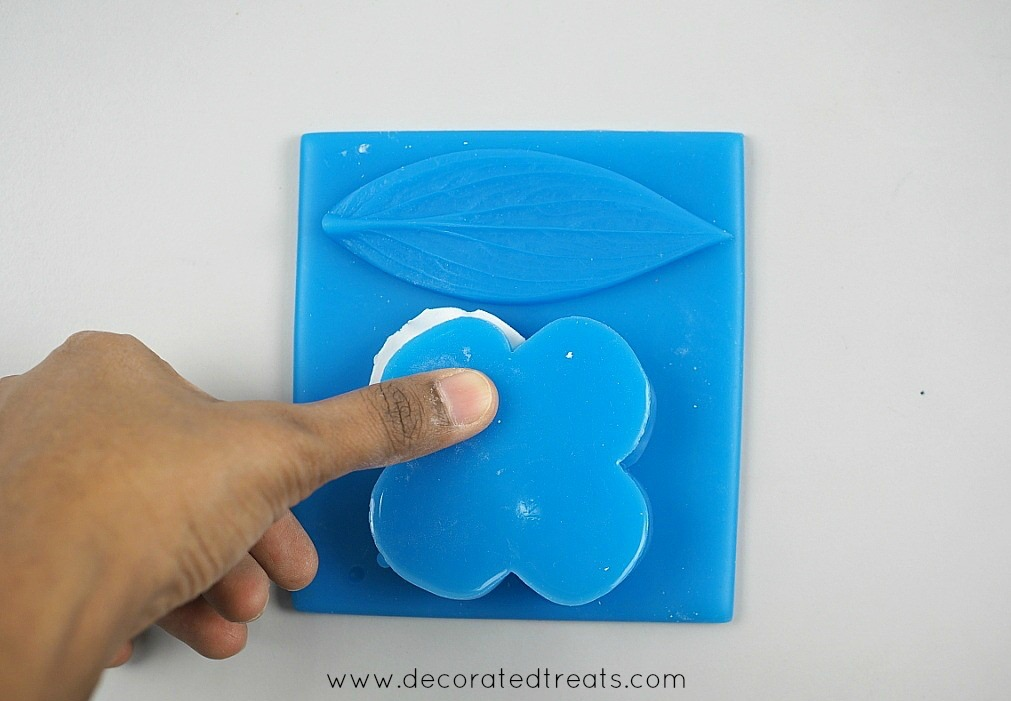 Pressing a blue veiner on a gum paste petal