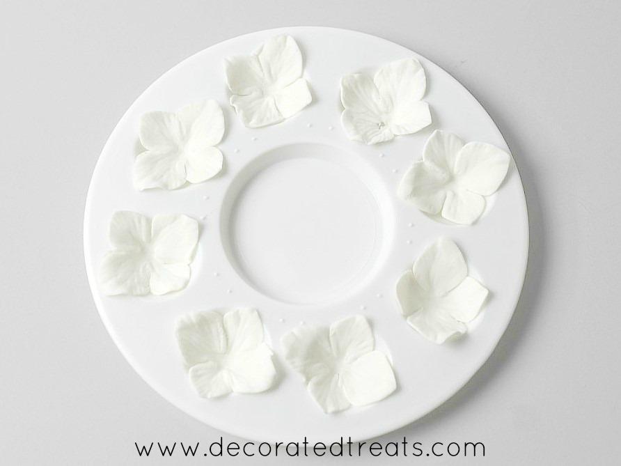 Gum paste hydrangea flowers on a paint palette.