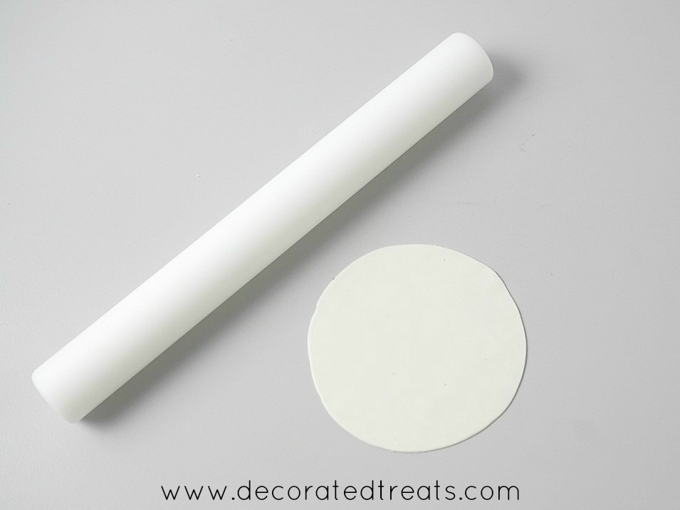 A piece of rolled gum paste with a small white rolling pin on the side