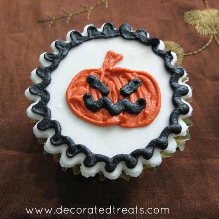 A cupcake decorated with an orange Halloween pumpkin design
