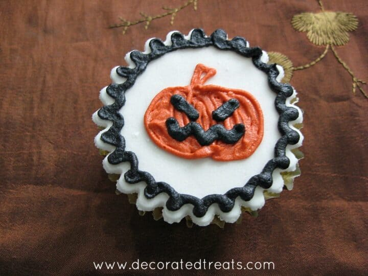 A cupcake decorated with an orange Halloween pumpkin design