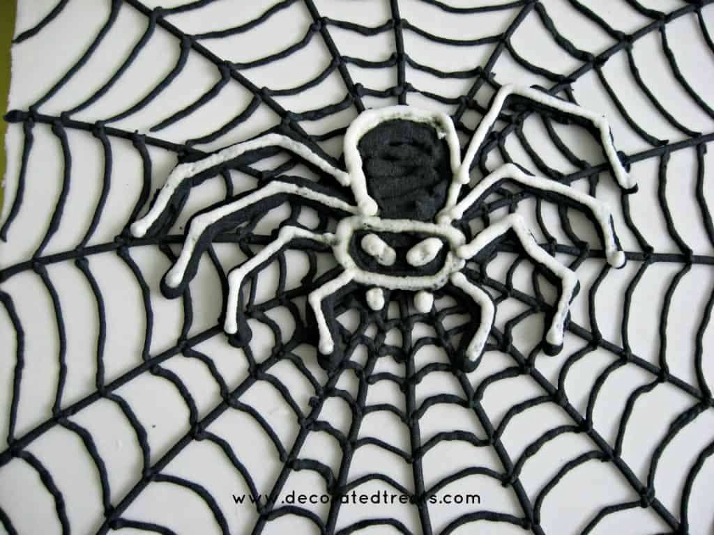 A white square cake with a royal icing spider web and a black piped spider