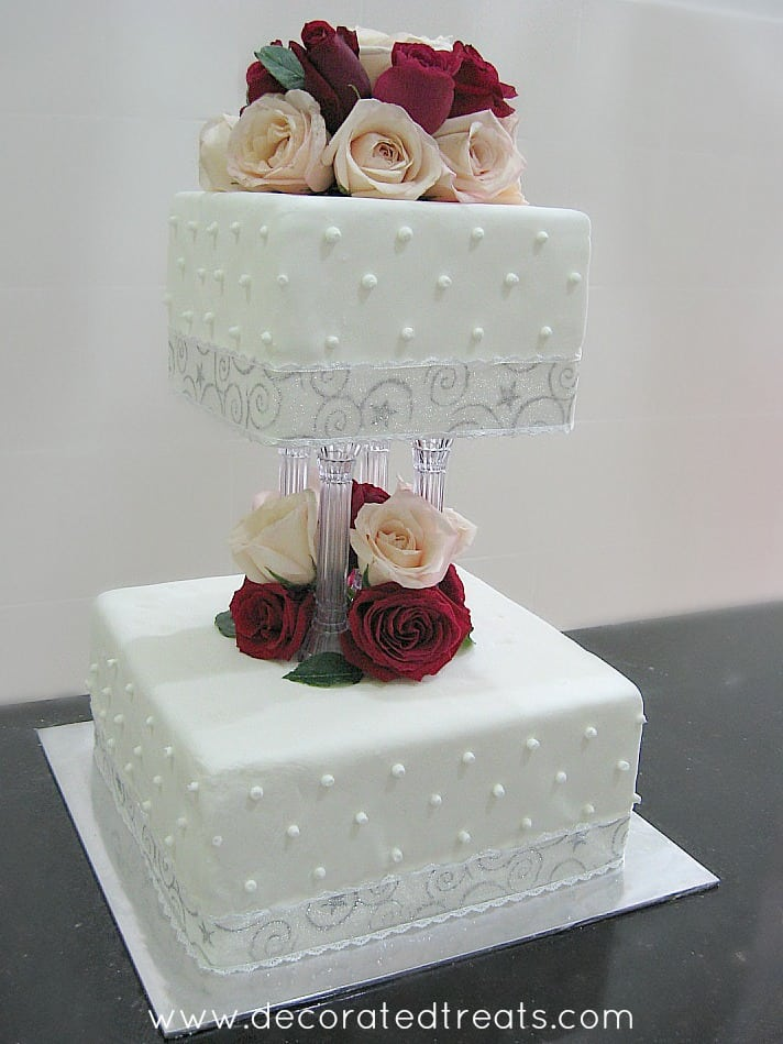 A 2 tier cake stacked on pillars