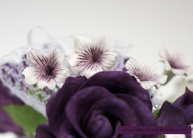 White filler flowers in a bouquet of purple gum paste roses