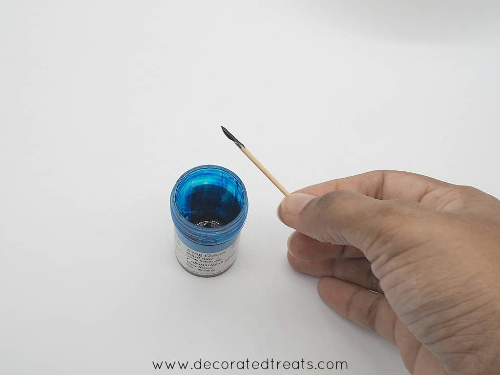 A toothpick dipped in a bottle of blue food color.