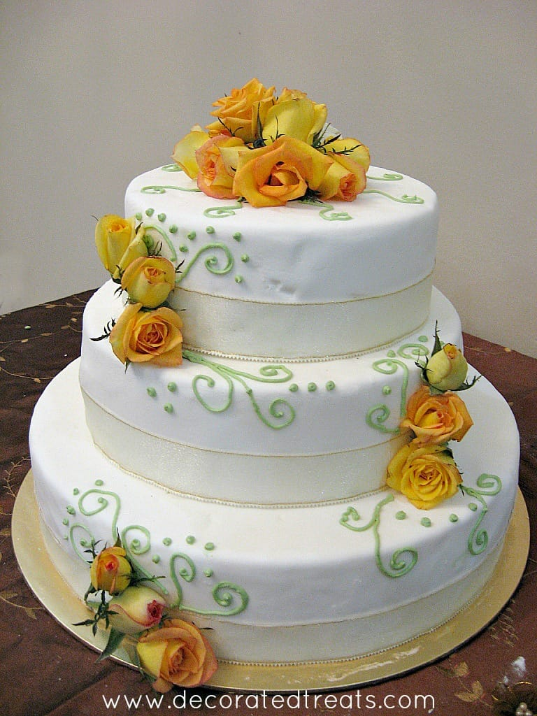 A 3 tier cake with yellow roses