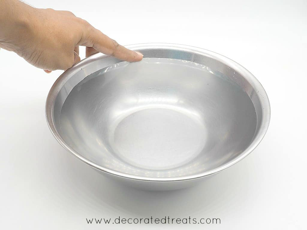 Pointing to the water level in a bowl filled with water