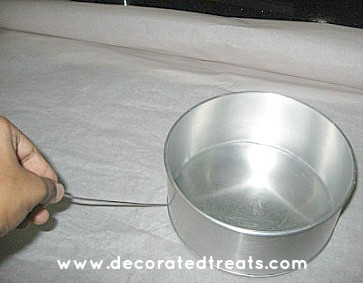 Using a skewer to mark the bottom of a cake tin onto a parchment square