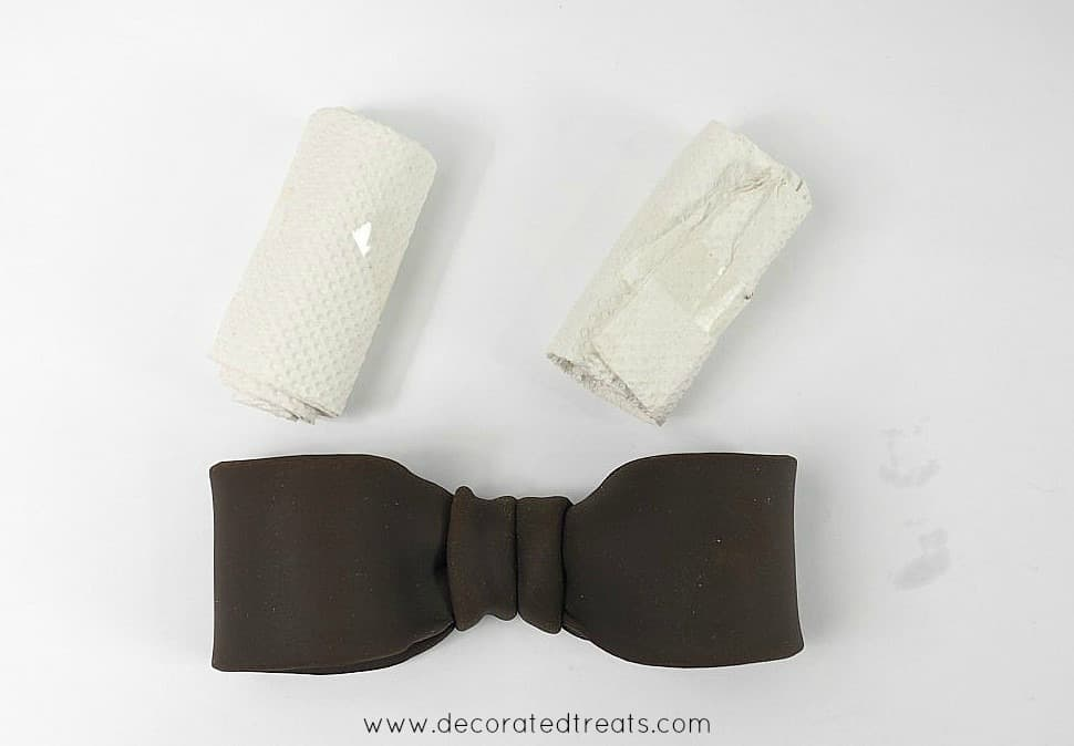 Brown fondant bow with 2 tissue rolls on the side
