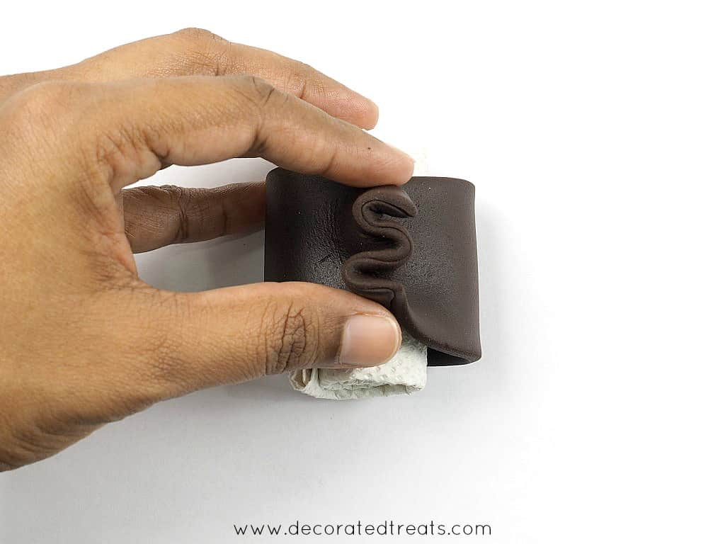 A strip of brown fondant wrapped around a small roll of tissue and the edges gathered