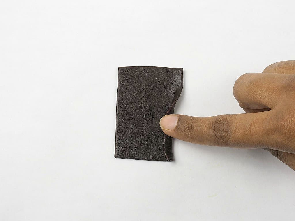 Rolling the edge of a rectangle brown fondant