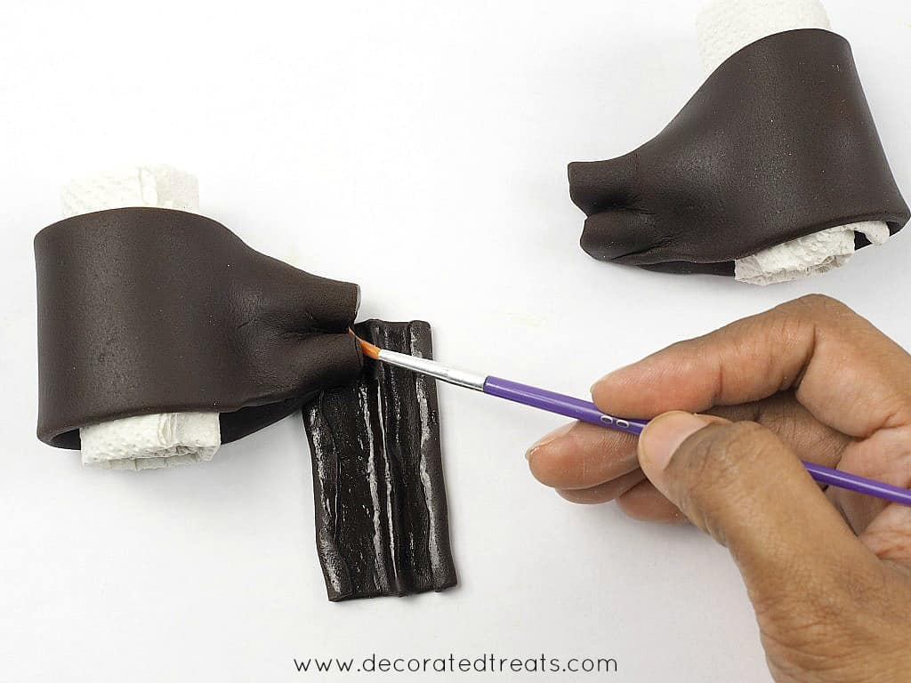 Brushing the edges of brown fondant bow