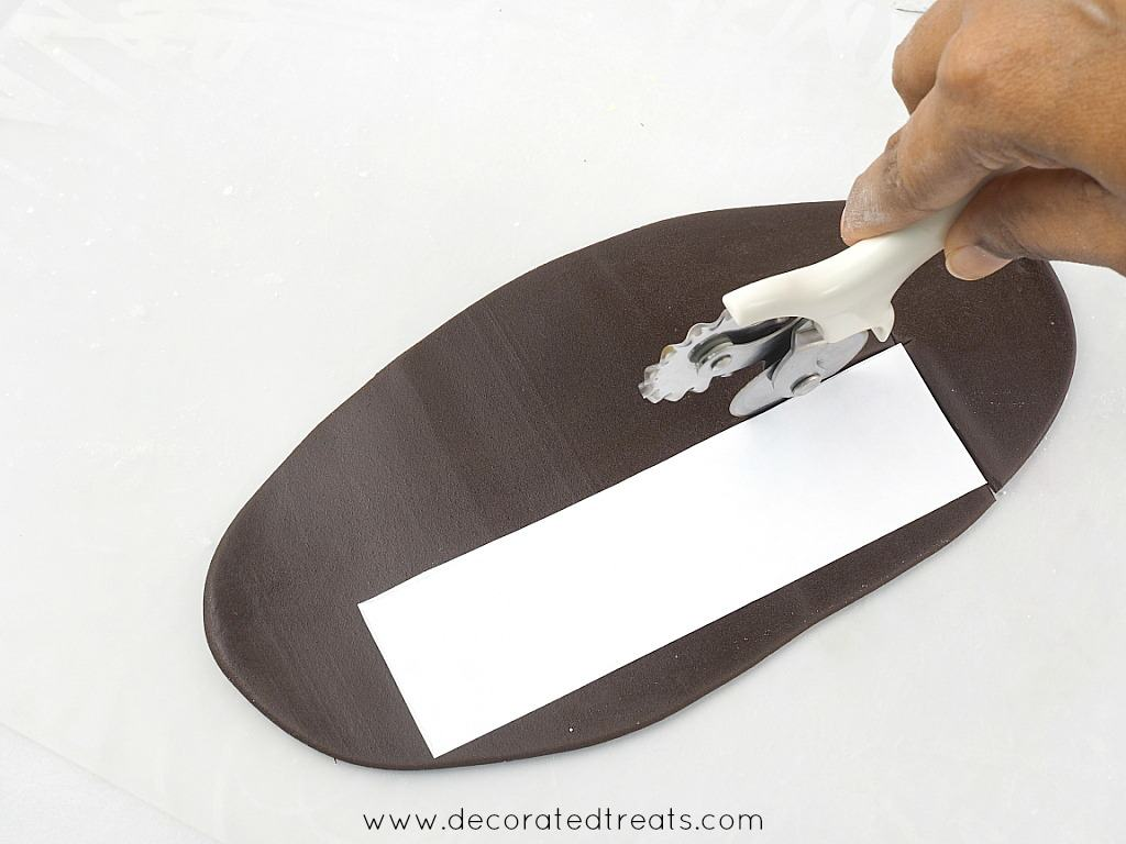 Cutting along a rectangle paper template on a rolled brown fondant with a pizza cutter
