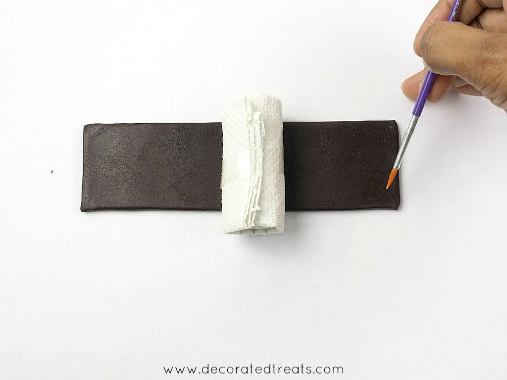 Brushing the edge of a brown rectangle fondant strip with a small roll of tissue on it