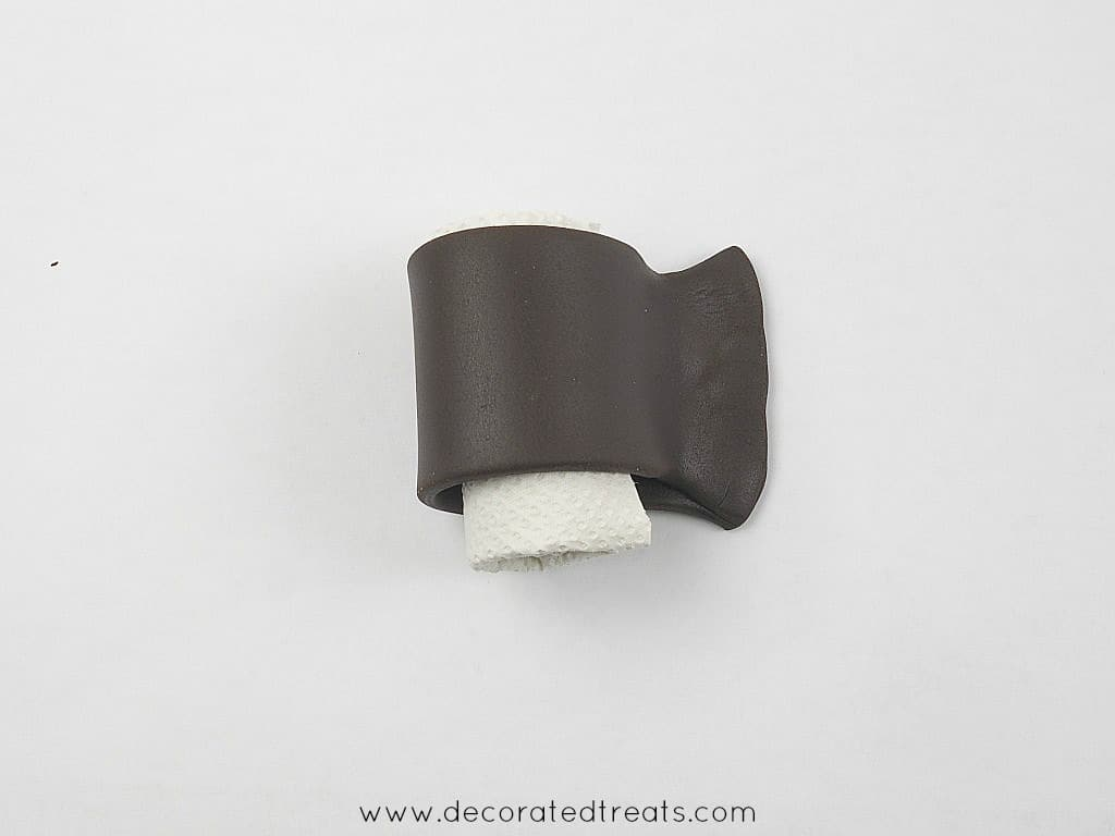 A strip of brown fondant wrapped around a small roll of tissue and the edges pinched