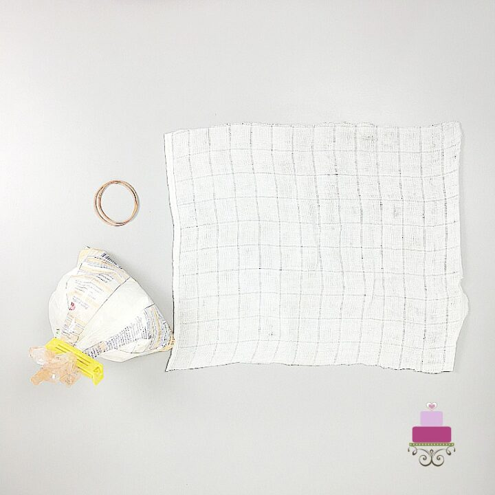 A rectangle piece of white cloth on a white background. On the side is a small bag of cornstarch