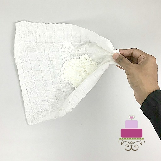 Gathering edges of a white cloth into a pouch