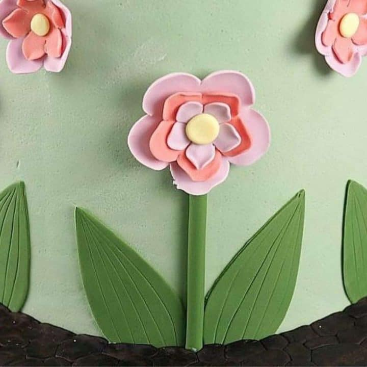 The bottom tier of a cake decorated with pink and purple flowers, leaves and stems