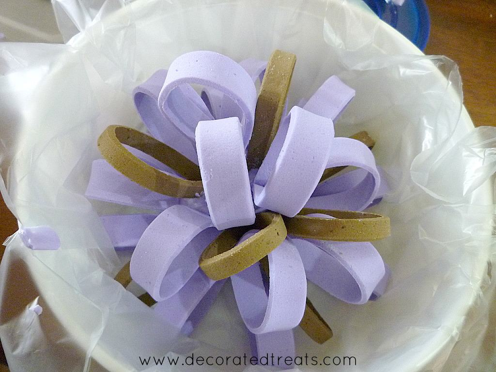 A round row of brown and violet fondant loops in a plastic lined white container