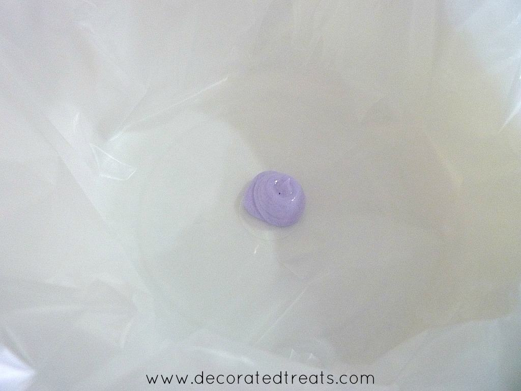 A blob of violet icing in a white container lined with plastic sheet