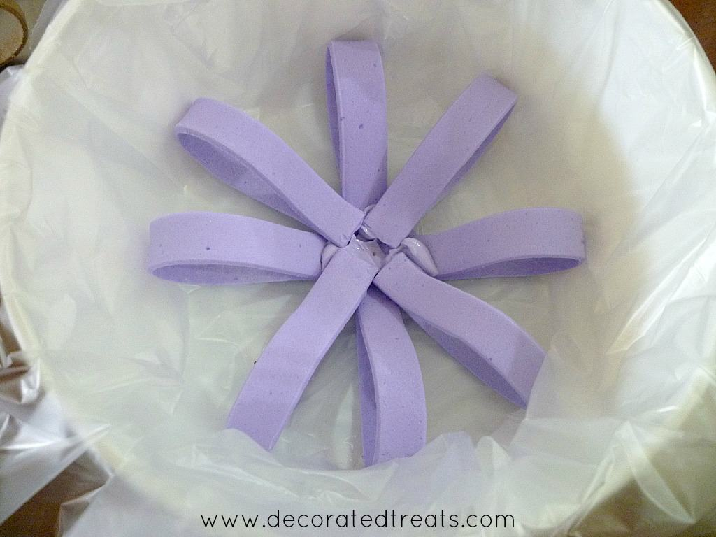 A round round of violet fondant loops in a plastic lined white container