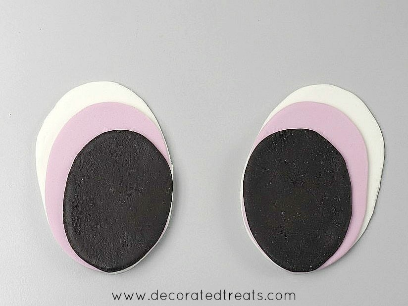 A set of 2 oval fondant cutouts in white, purple and dark brown stacked together