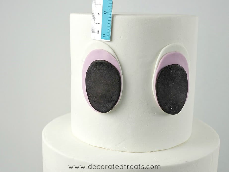 Using a ruler to measure the spacing from the top of the cake to the fondant eyes on the top tier cake