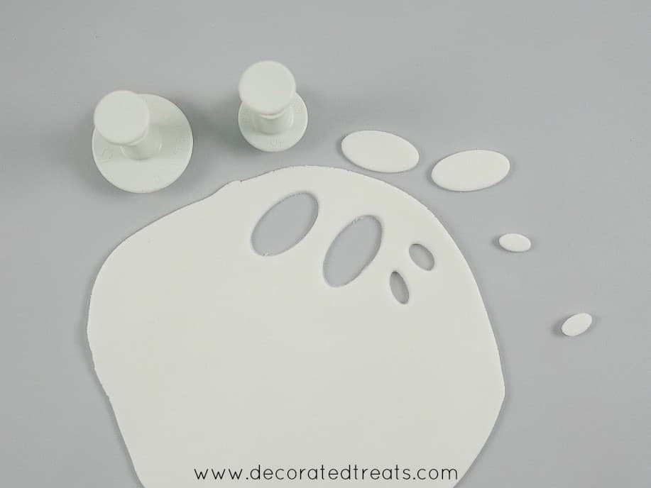 Rolled white fondant with oval cut outs. Oval plunger cutters are in the background