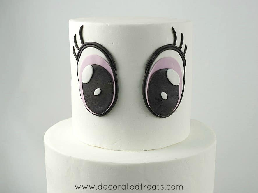 A two tier white cake with 2 large fondant eyes on the top tier