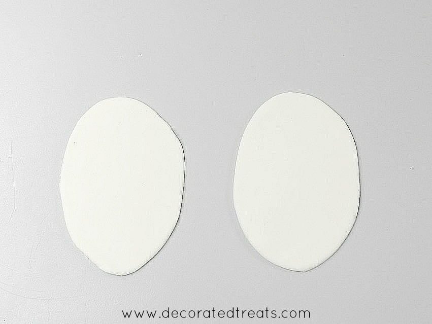 2 oval shaped white fondant cut outs