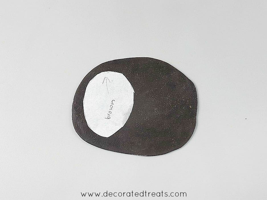 Oval paper template on brown fondant