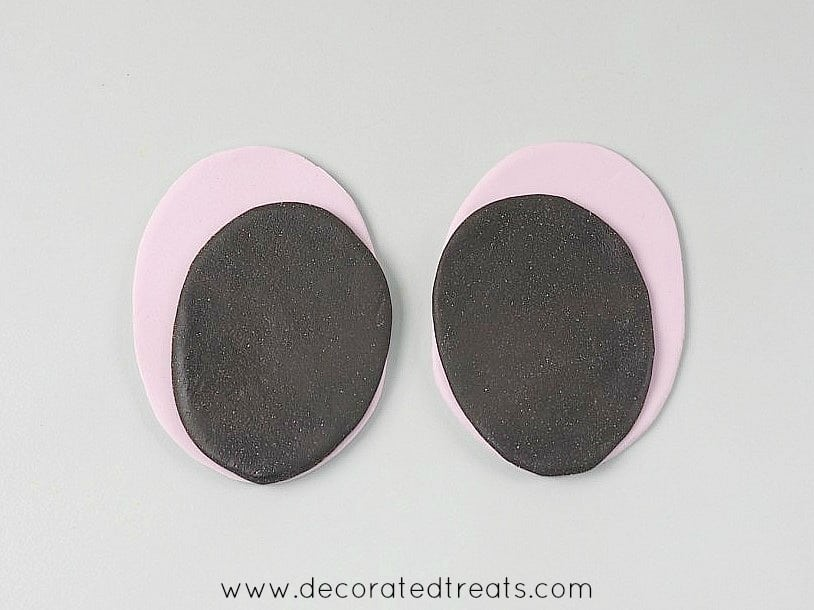 2 oval brown fondant cut outs on slightly larger purple oval fondant cutouts