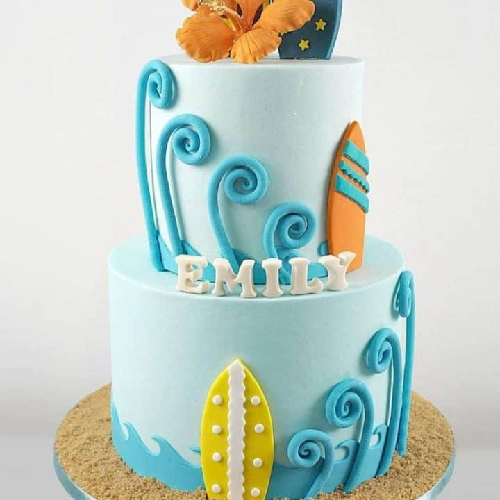 A two tier beach themed cake in blue, orange and yellow, with orange gum paste hibiscus and fondant surfboards