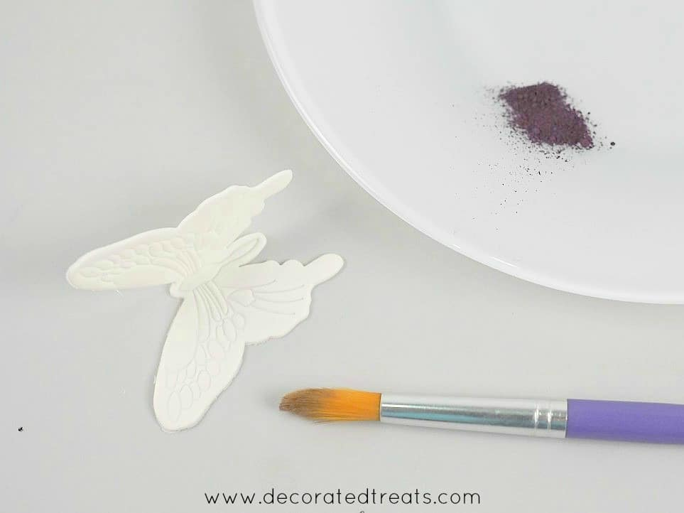 A white gum paste butterfly cake decoration with a paint brush and a plate of violet dust