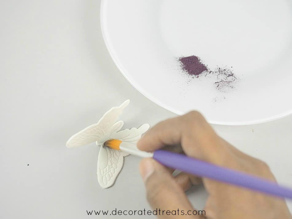 Using a brush to dust the center of a gum paste butterfly. In the background is a plate of violet dust