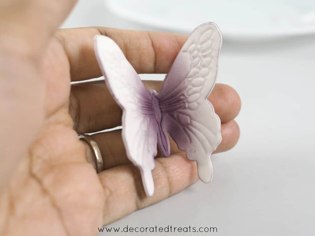 Gum paste violet butterfly held in hand
