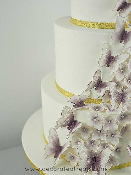 A multi tier cake with violet gum paste butterflies and hydrangeas