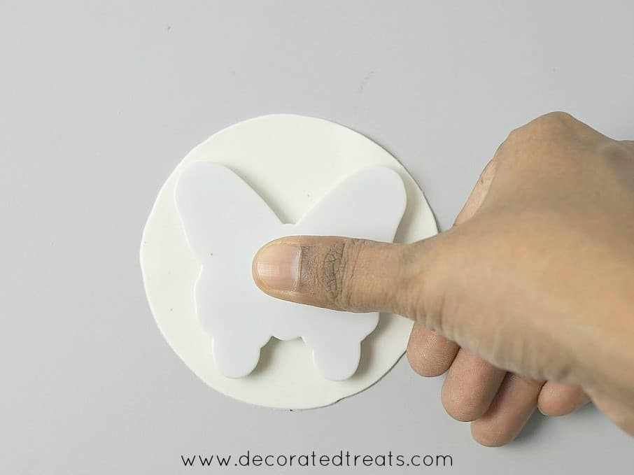 Pressing a butterfly cutter on a piece of round gum paste
