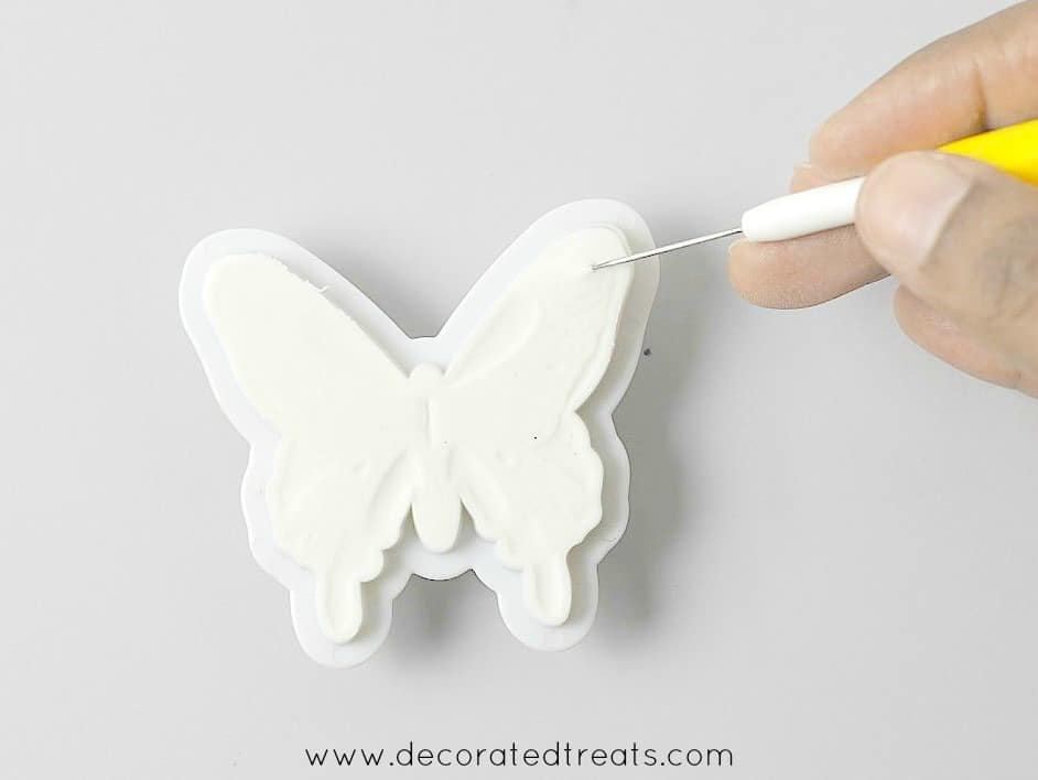 Using a needle tool to remove gum paste butterfly from its cutter