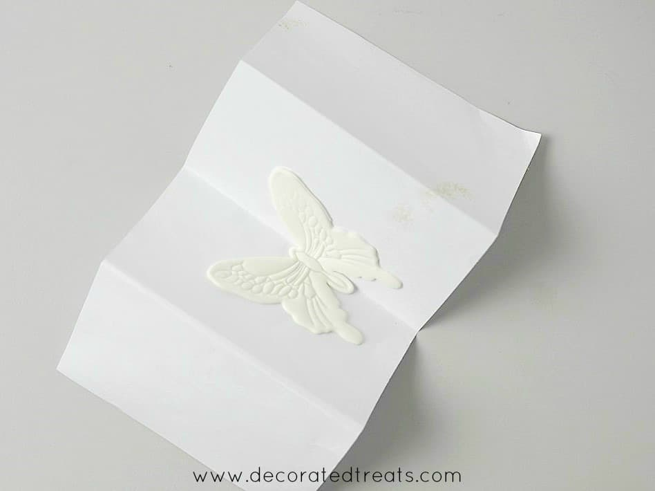 Gum paste butterfly on a piece of folded paper