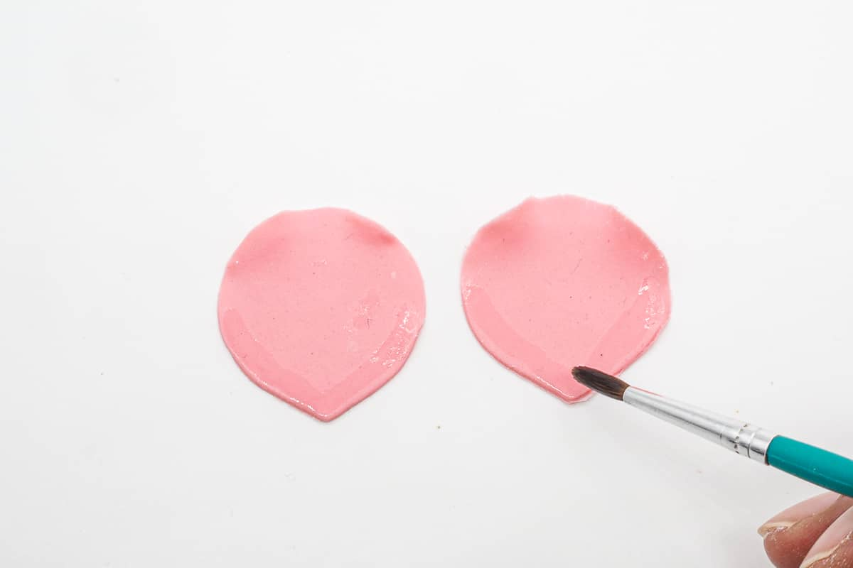 2 cone shaped gum paste petals with a brush brushing glue around the edges