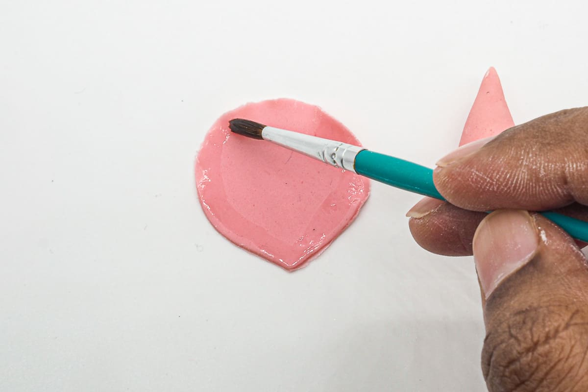 Using a brush to apply glue to pink gum paste petal