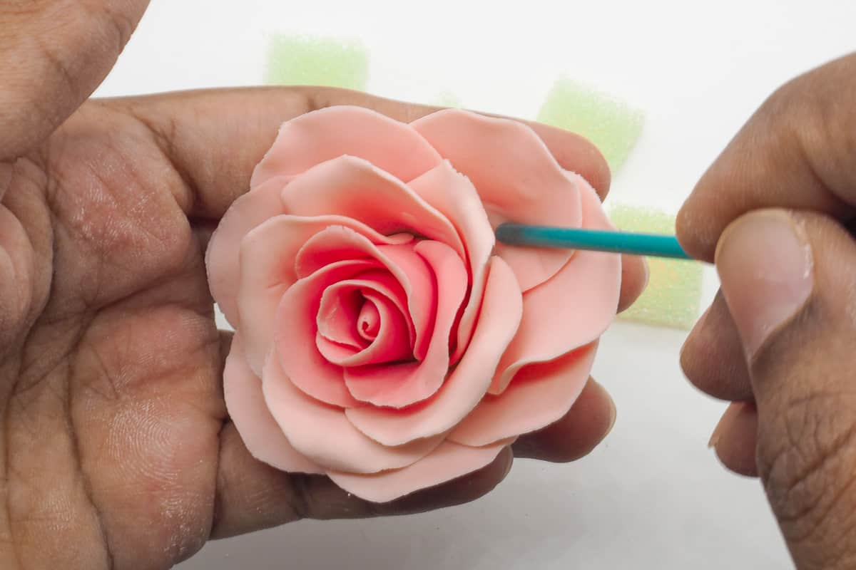 Adjusting gum paste rose petals with the back of a brush