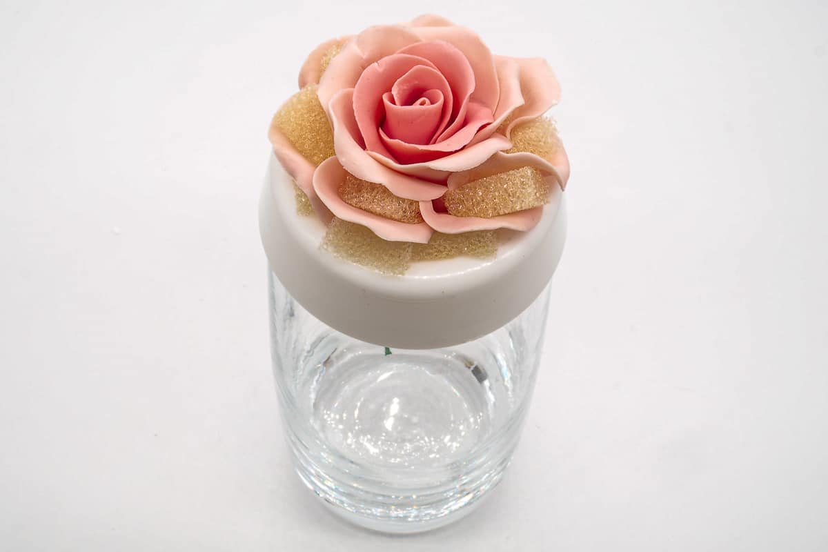 Gum paste rose with tiny sponge piece between petals, placed on a flower former on top of a drinking glass
