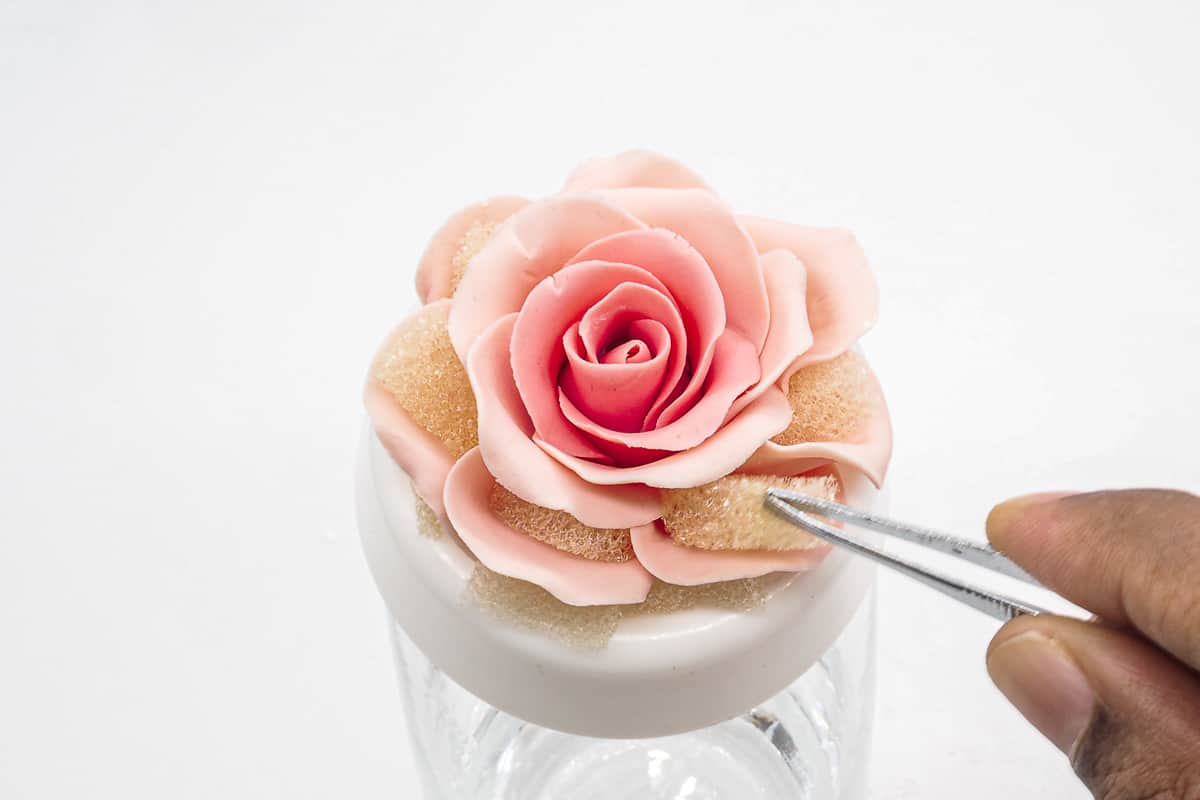 Removing sponge pieces between rose petals with a tweezer