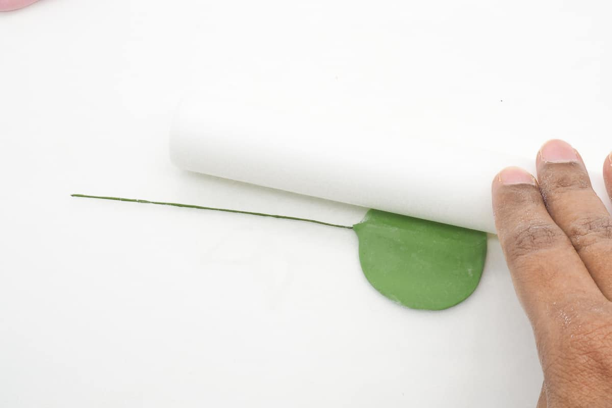 Rolling green paste with a small white rolling pin